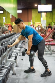Man exercising with arm weights in gym