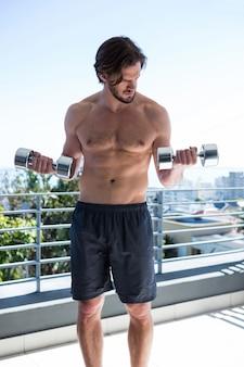 Человек упражняется с гантелями на балконе