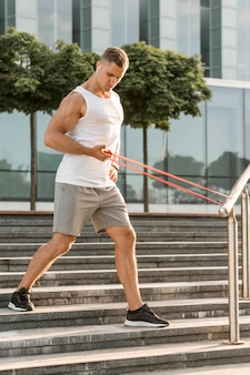 Man exercising with a red stretching band outside
