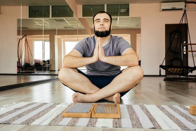 Мужчина занимается йогой, медитируя, сидя руки соединились на полу возле доски садху