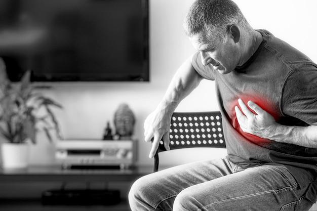 男性は心臓発作によって引き起こされる胸の痛みを経験します。黒と白の孤立した背景を持つ老人の心臓病。高齢者のための医療保険の概念。