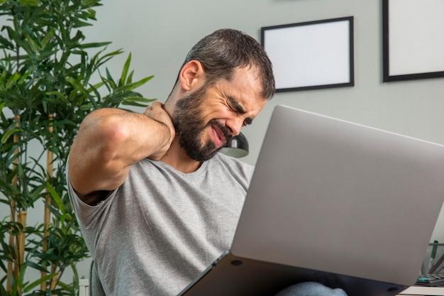 Человек испытывает боль в шее, работая дома на ноутбуке