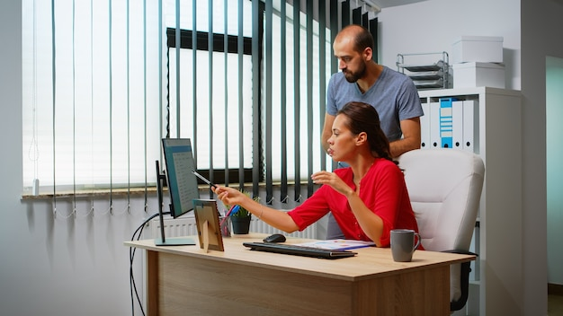 Man explaining solution of problem to hispanic colleague in front of pc. team working in professional workplace in personal corporate company typing on computer keyboard looking pointing at desktop