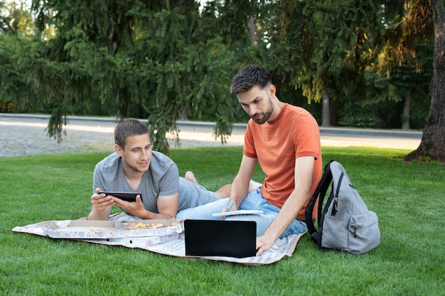 Man explaining something to her friend in laptop. happy students studying at park and smiling.
