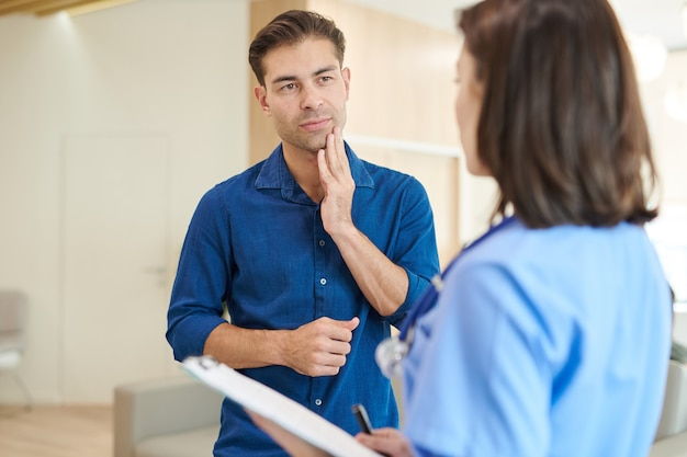 看護師に症状を説明する男