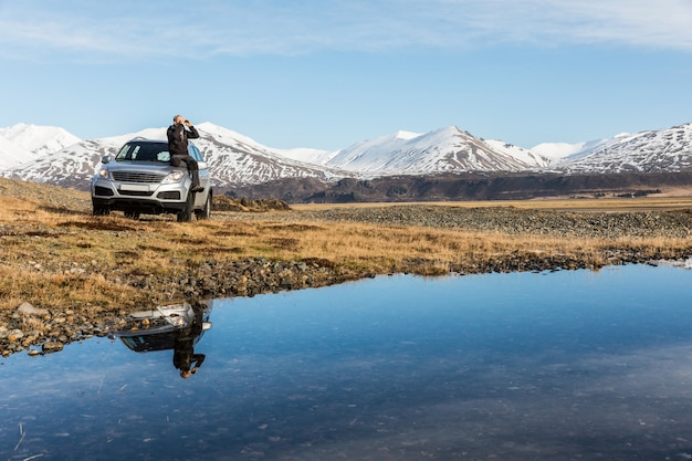 Man explorer in iceland sitting on the car