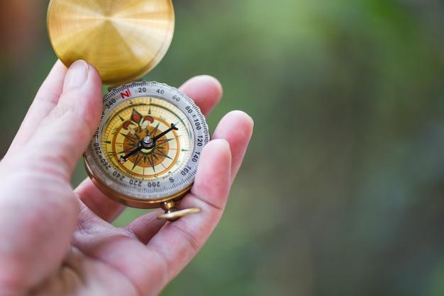 Человек исследователь поиск направления с компасом для карты - навигационный компас путешествия и туристическая концепция