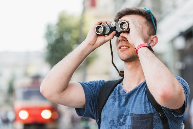 Man exploring city with binoculars