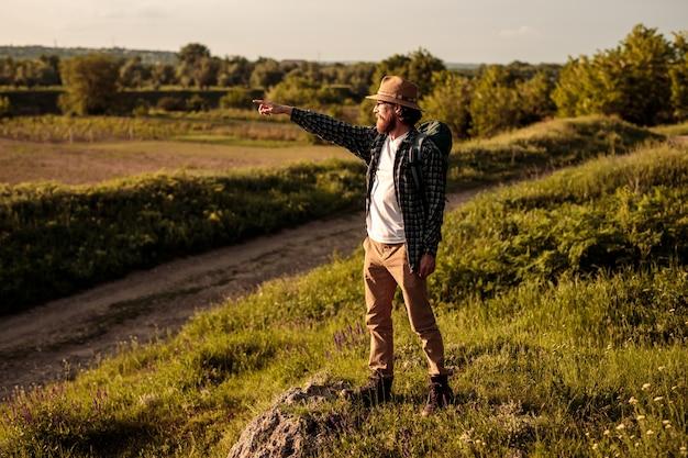 風景を探索し、離れて指している男