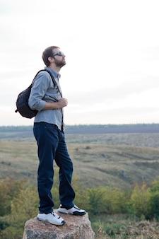 열린 시골에서 바위 위에 서있는 배낭으로 탐험하는 남자