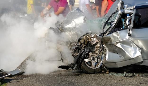 男は消火器で車を消火します。交通事故後の損傷した車両のクローズアップ。