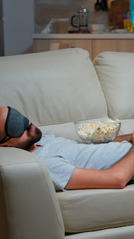 Человек маска для сна засыпает во время просмотра фильма