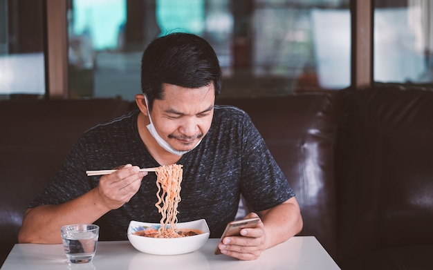 Man in face mask eating a noodle and holding a smart phone at home .  stay at home for protect 2019-ncov virus or covid-19 concept. 16:9 style