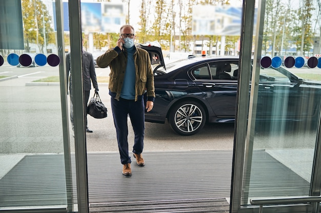 Man in a face mask followed by his private driver