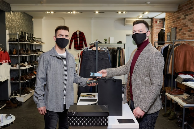 A man in a face mask is posing while using a smartphone to pay by nfc for purchases in a store. a shop assistant in a mask is holding out a terminal for contactless paying to a customer in a boutique