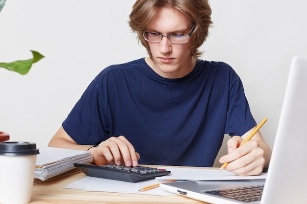 Man faces financial crisis, studies notification from bank, calculates figures. male student studies math, prepares report