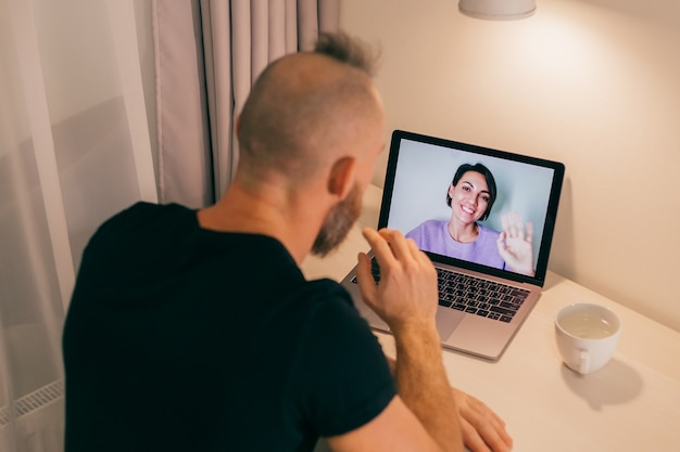 Man facetime at home, calling his friend wife girlfriend from laptop in bedroom.