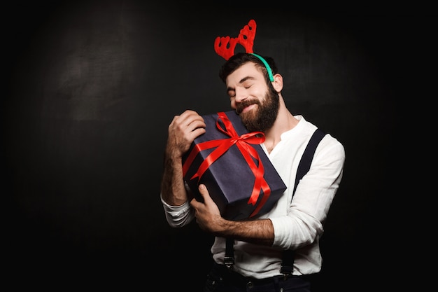 Man in fake deer horns holding christmas gift box over black.