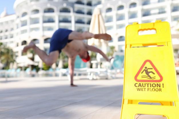 Man falling near yellow plastic sign caution wet floor closeup