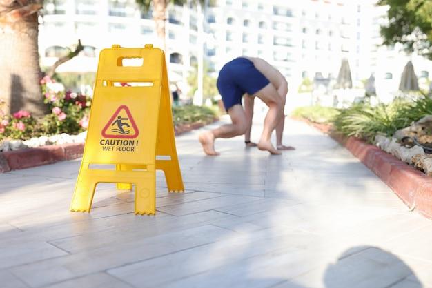 Man falling on tile near sign with inscription caution wet floor closeup