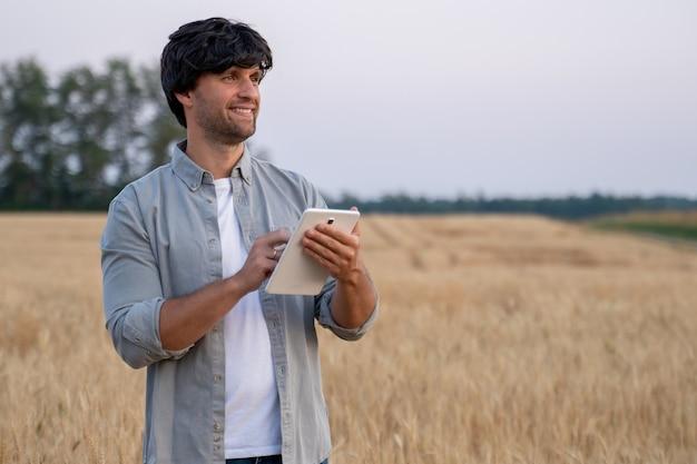 Фермер человек, использующий цифровой планшетный компьютер, стоящий на пшеничном поле и использующий приложения и проверяющий качество ...