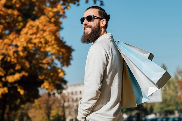 Man fashion style bearded hipster guy with shopping bags enjoying autumn sunny day
