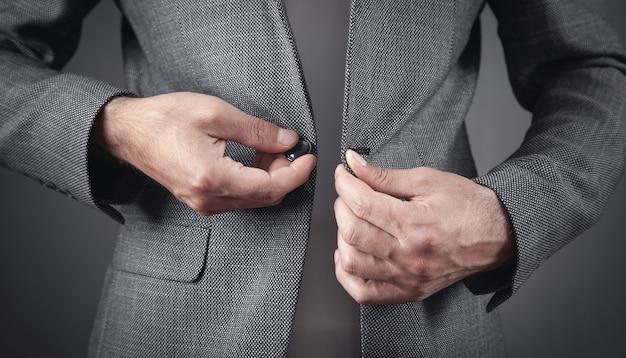 スーツのボタンを締める男。ファッション