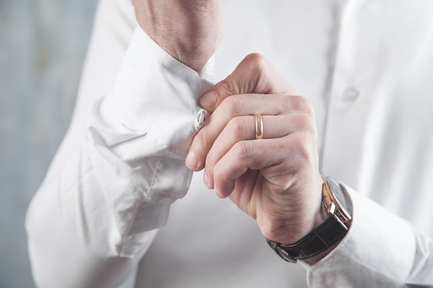 Man fastening buttons on shirt.