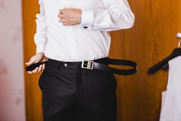 그의 바지에 그의 벨트를 고정하는 남자