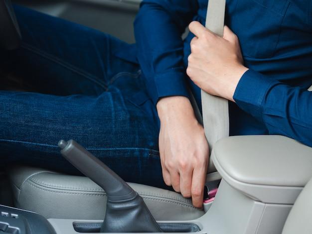 Человек, пристегивающий ремень безопасности в машине