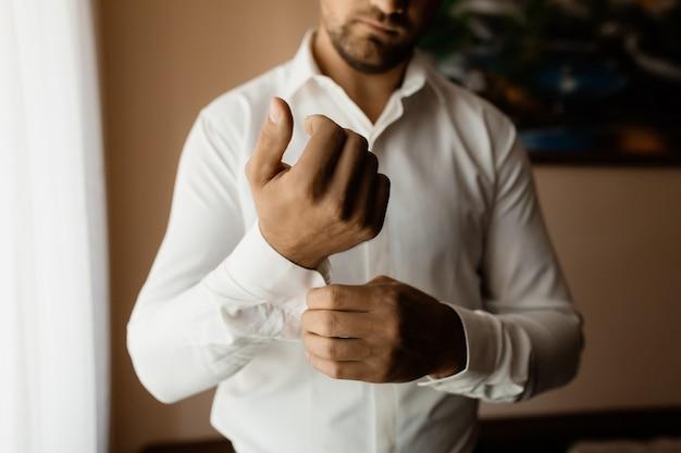 Мужчина застегивает пуговицу на рукаве рубашки