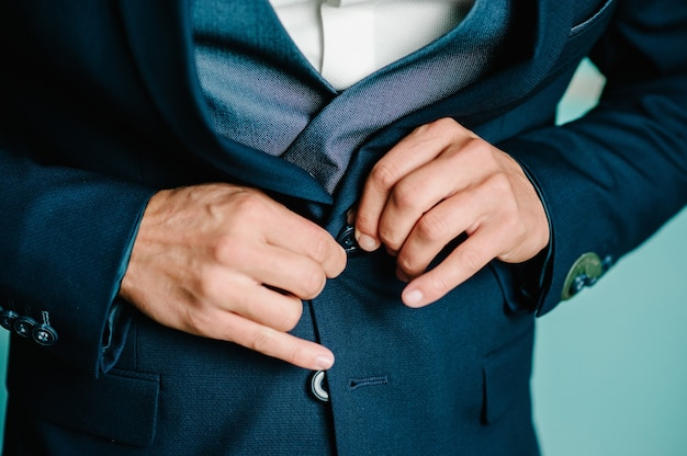 Man fastens the buttons jacket. the groom in a suit, shirt.