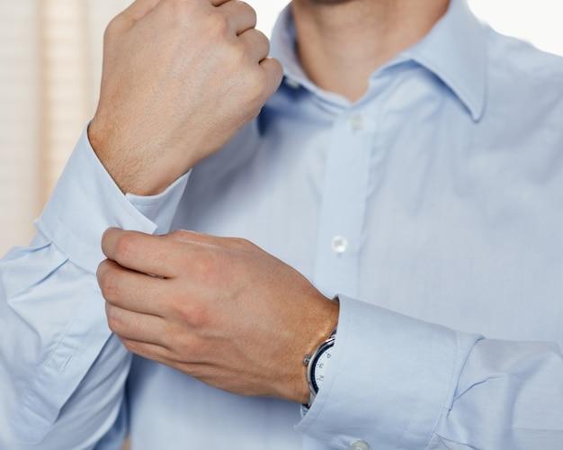 男はカフスボタンのクローズアップを締めます。外出の準備をしているビジネスマンや婚約者。