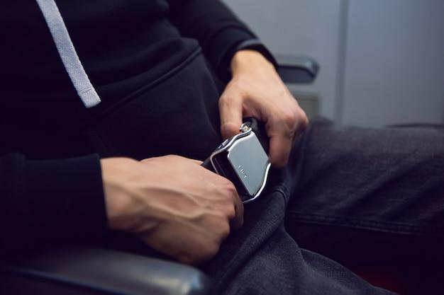 Мужчина пристегивает ремень безопасности в самолете в черной толстовке с капюшоном