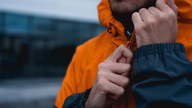 A man fastens his work uniform. orange worker uniform - hands close up