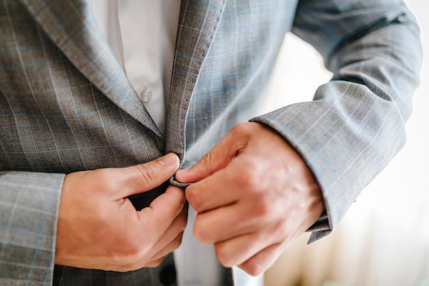 Человек застегивает пуговицы. жених в костюме, рубашке стоит на белом фоне. закройте вверх.