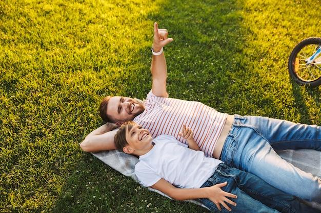 Отец человек отдыхает с сыном на открытом воздухе в парке указывая.