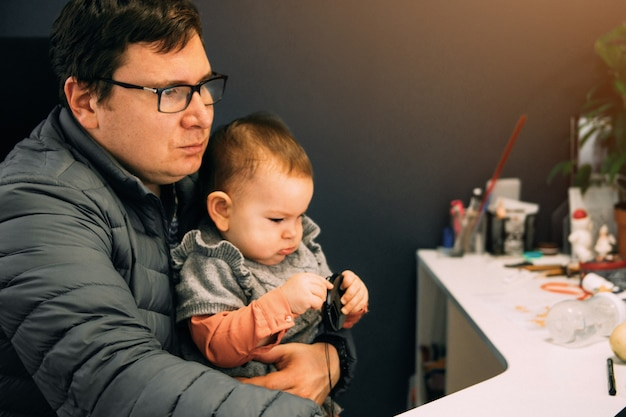 Man father with baby in carrier working at office or home with computer at the desk