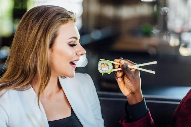 レストランのテラスでガールフレンドのために巻き寿司を食べている男。食品のコンセプト。