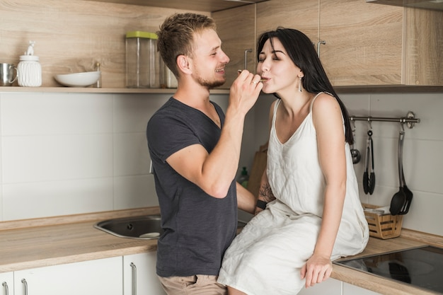Man feeding food from spoon to his wife in the kitchen