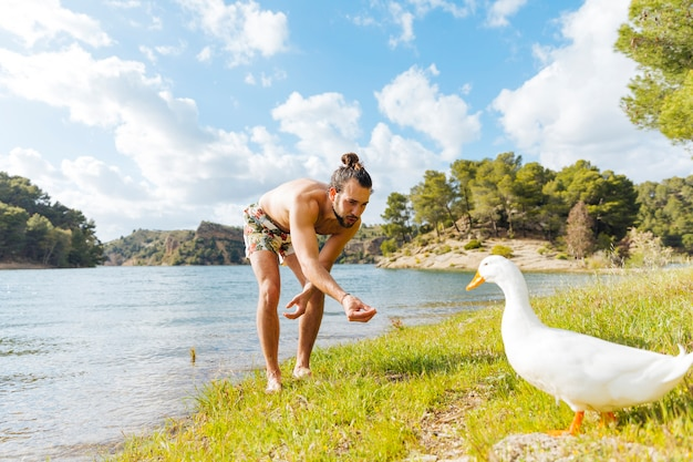 Man feeding goose on shore