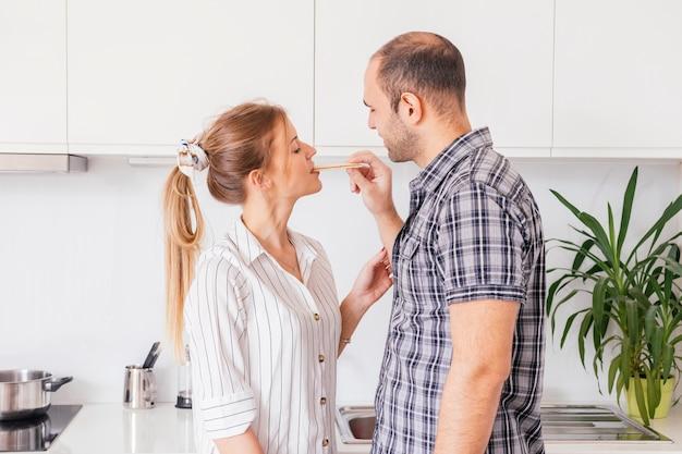 Man feeding graham cracker to his girlfriend in the kitchen