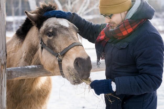 Man feeding horse on ranch