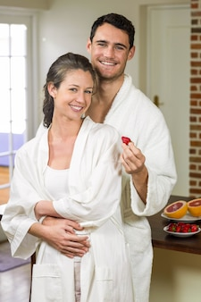 Man feeding strawberry to woman in kitchen