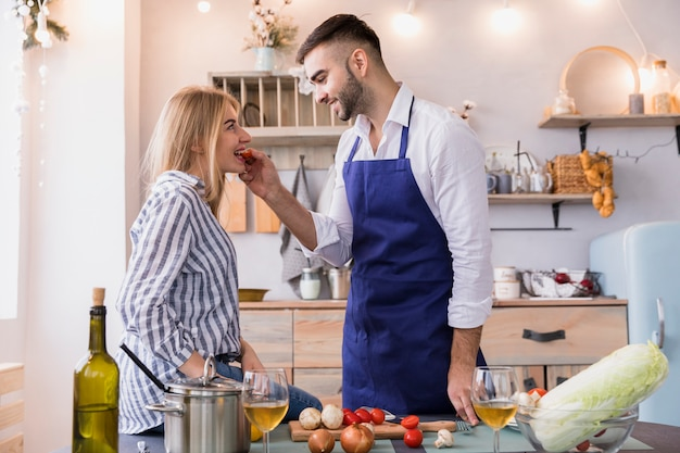 Man feeding woman with tomatoes in kitchen