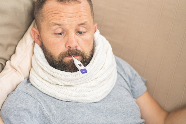 Man feeling bad lying in bed and looking the thermometer