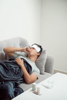Человек плохо себя чувствует, лежа на диване и кашляет
