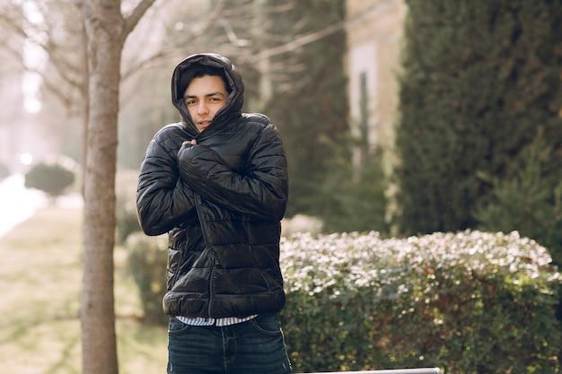 Uomo che si sente freddo con la giacca invernale nera nel parco. foto di alta qualità