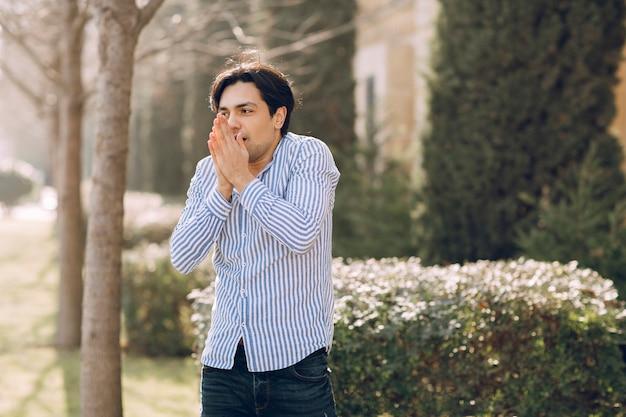 公園でシャツを着て寒さを感じる男。高品質の写真