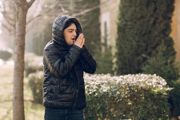 Человек чувствует себя холодно в черной зимней куртке в парке. фото высокого качества